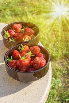 花崗岩のテーブルの上の黒いプレートで、日光に照らされた新鮮なイチゴ。