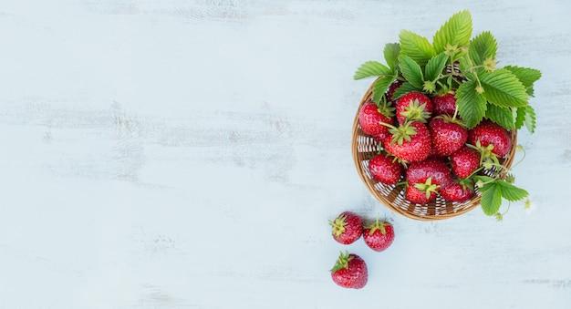 素朴な木製の背景の上面図のバスケットに新鮮なイチゴ。白い木製のテーブルのモックアップで健康食品。テキスト用のコピースペースを備えた、おいしく、甘く、ジューシーで熟したベリーのバクグロウン。