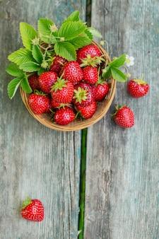 素朴な木製の壁の上面図のバスケットに新鮮なイチゴ。木製のテーブルモックアップの健康食品。テキスト用のコピースペースを備えた、美味しくて甘くてジューシーで熟したベリーの壁。