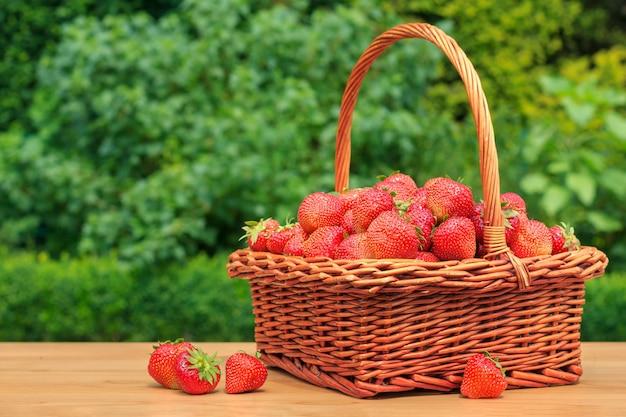 Свежая клубника в корзине на деревянный стол в саду