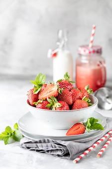 Свежая клубника в миску и веточки мяты на белом бетонном столе. ингредиент для смузи. бутылка молока, красная стеклянная кружка и блендер.