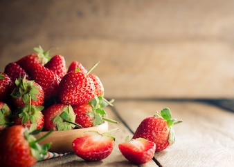 Fresh strawberries in a bowl on wooden background.