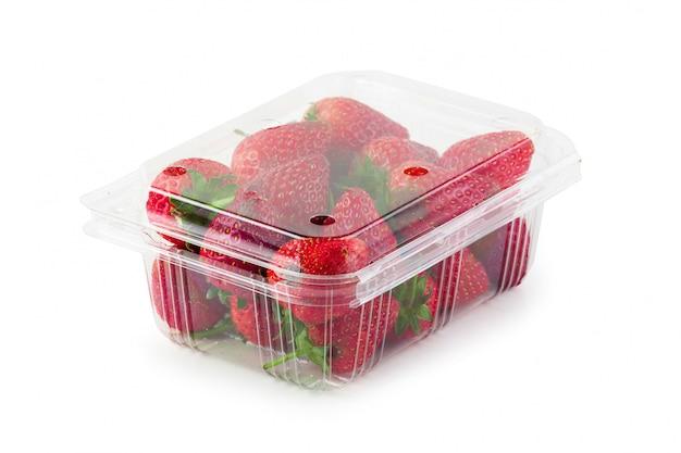 白い背景で隔離された明確なプラスチック製の箱で新鮮なイチゴ