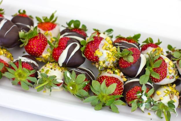 チョコレートとピスタチオ、白い皿に新鮮なイチゴ Premium写真