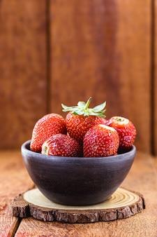 나무 표면 및 복사 공간 수제 점토 그릇에 신선한 딸기