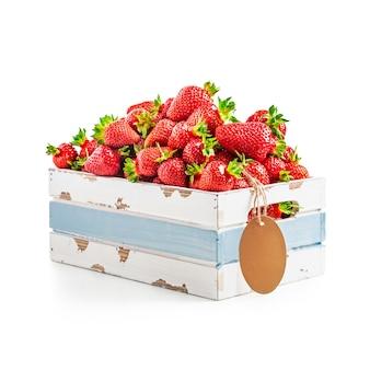 흰색 배경에 태그 레이블이 분리된 오래된 나무 상자에 있는 신선한 딸기. 건강한 식생활. 클리핑 패스가 있는 단일 개체