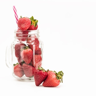 Fresh strawberries in jar on white background