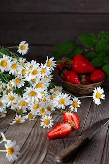 ナイフと夏の花カモミールと木製のテーブルの上の新鮮なイチゴ。夏の写真