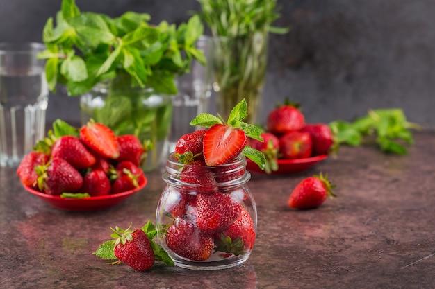 Свежая клубника на стеклянной банке заделывают. вкусные, сладкие, сочные и спелые ягоды с местом для текста