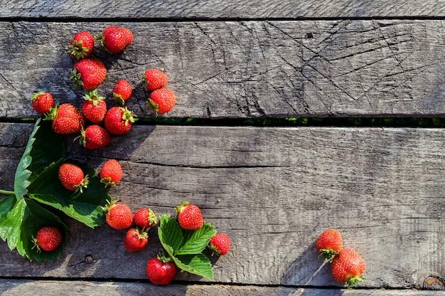 古い木製の背景に、新鮮なイチゴ