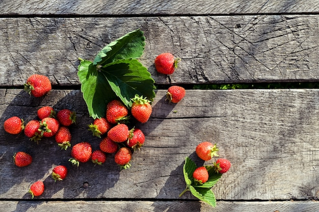 コピースペースを持つ素朴な木製の背景に、新鮮なイチゴ。テキストのためのスペース