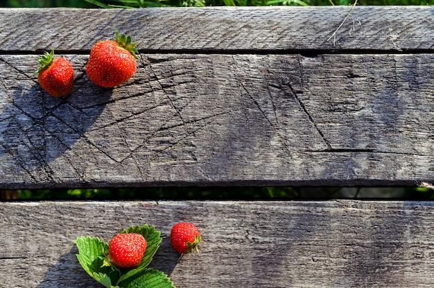 コピースペースを持つ素朴な木製の背景に、新鮮なイチゴ。上面図