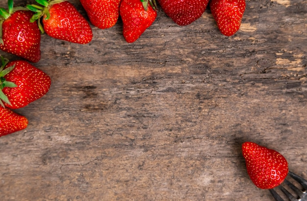 Fresh strawberries and one berry on fork still life on dark wooden background