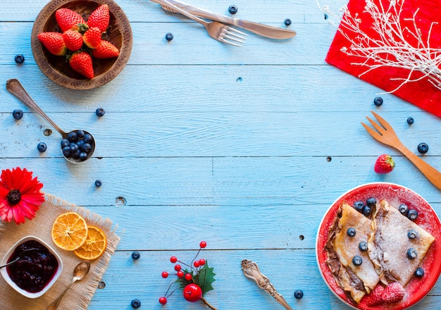 Fresh strawberries pancakes or crepes with berries and chocolate on blue wooden background
