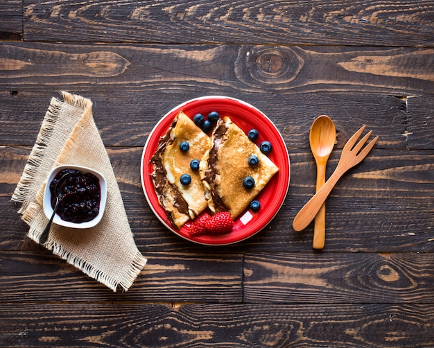 Fresh strawberries pancakes or crepes with berries and chocolate
