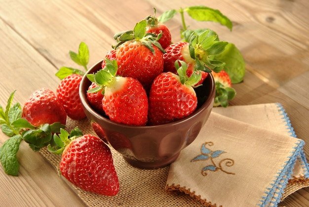 Fresh strawberries on a plate and brown fabric