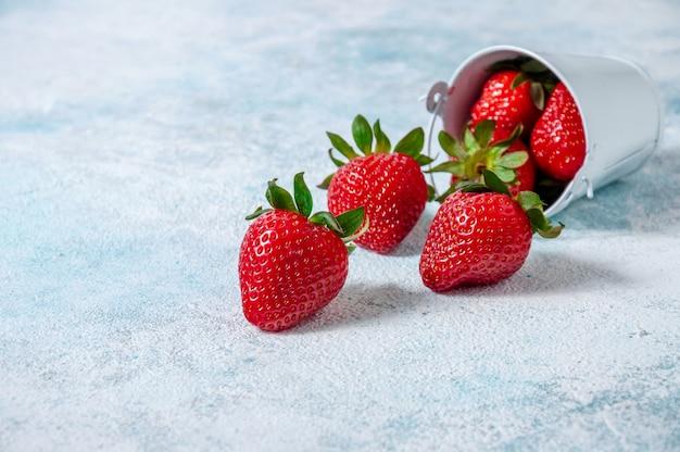 Fresh strawberries in small white bucket board.
