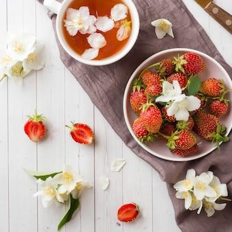 Fresh strawberries and tea with jasmine flowers