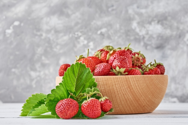Fresh strawberries in a wooden bowl and green leaves on gray