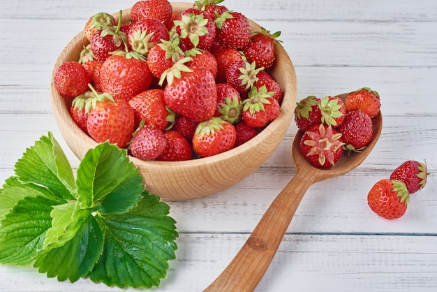 Fresh strawberries in a wooden bowl and spoon