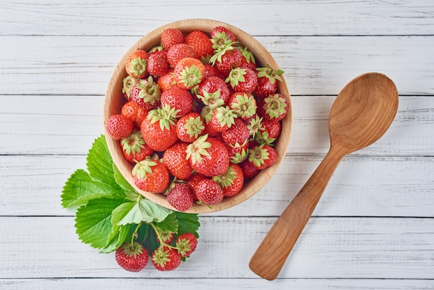 Fresh strawberries in wooden bowl with green leaves and wooden spoon on a gray background, top view