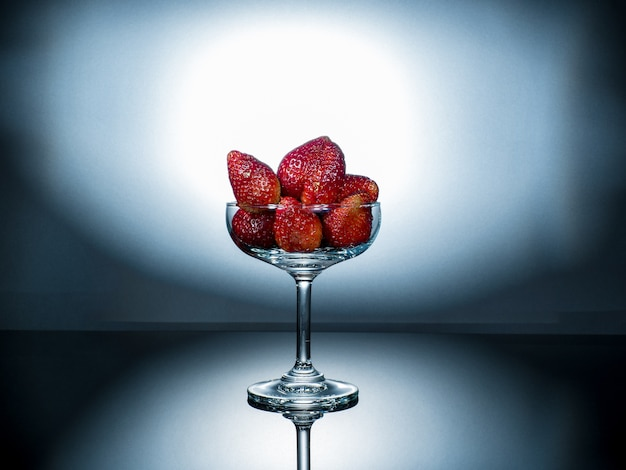 Fresh strawberry in the champaign glass,stand on reflective floor.