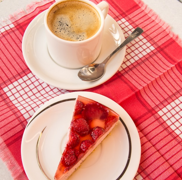 Fresh strawberry cheesecake and a cup of coffee with a spoon on a saucer, a top view of a piece of sweet dessert with strawberry berries in jelly, the concept of a delicious gourmet breakfast