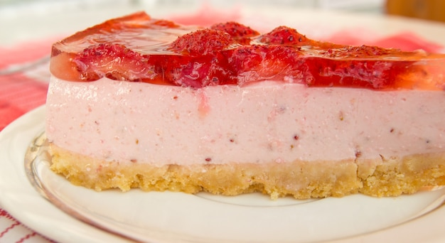Fresh strawberry cheesecake, one piece with layers, side view, close-up