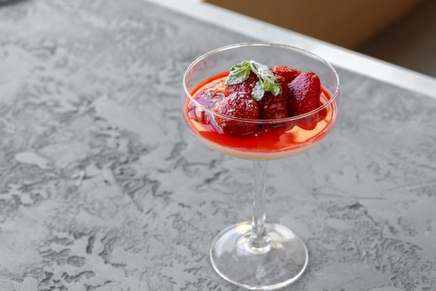 Парфе из свежих клубничных фруктов в стеклянной чашке на серой поверхности