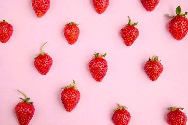 ピンクのシームレスなパターン、トップビューで新鮮なイチゴの半分