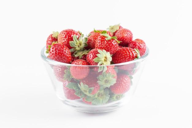 白い背景、側面図に分離された透明なボウルに新鮮なイチゴ