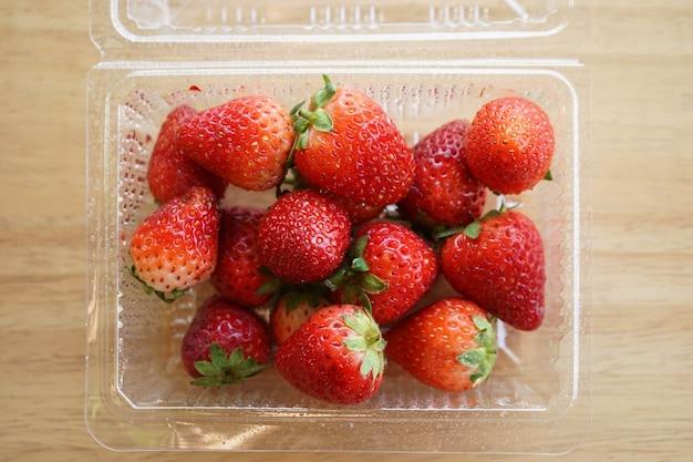 木製の机の上のプラスチックの箱に新鮮なイチゴ