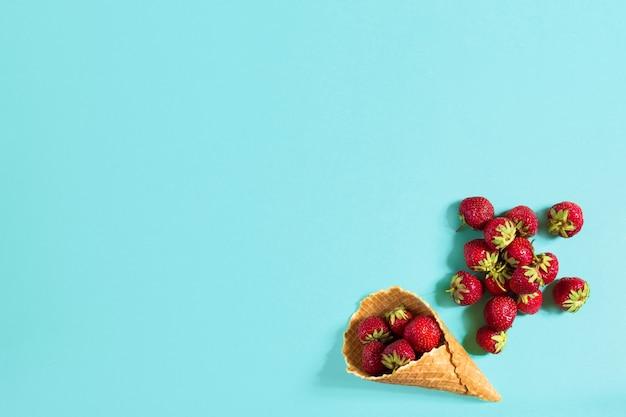 Свежая клубника в вафельном рожке. креативная концепция питания. плоская планировка, вид сверху. скопируйте пространство. плоский макет натюрморта