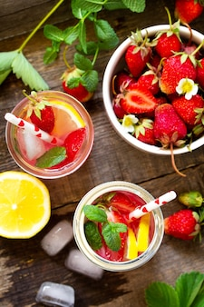 Fresh strawberry lemonade on rustic wooden table top view flat lay background