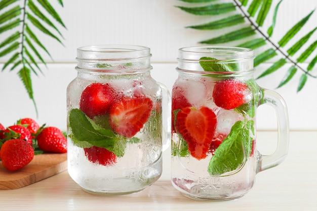 나무 탁자에 있는 두 개의 항아리에 얼음과 민트를 넣은 신선한 딸기 레모네이드 여름 다과 음료