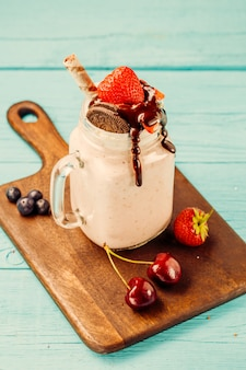 Fresh strawberry milkshake and berries on wooden desk on blue table.