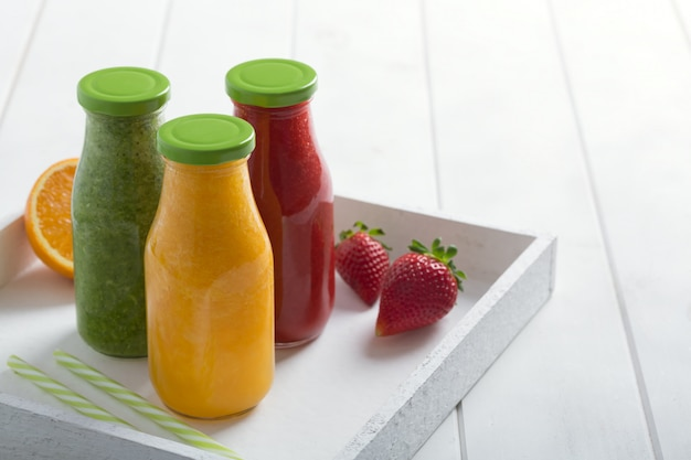 Fresh strawberry, orange and broccoli smoothie in bottles with fruits and vegetables