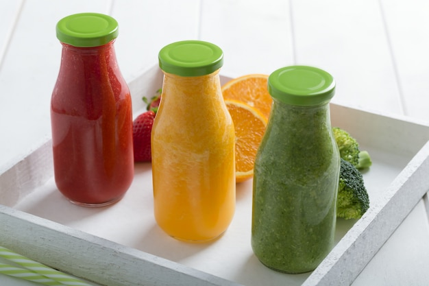 Fresh strawberry, orange and broccoli smoothie in three bottles with fruits and vegetables