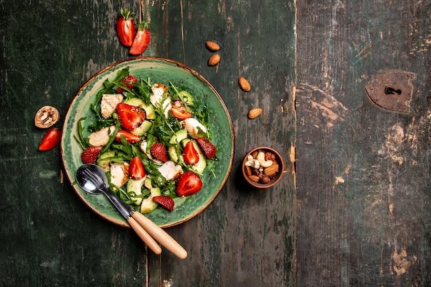 Салат из свежей клубники с рукколой, курицей, авокадо и клубникой. баннер меню рецепт место для текста, вид сверху