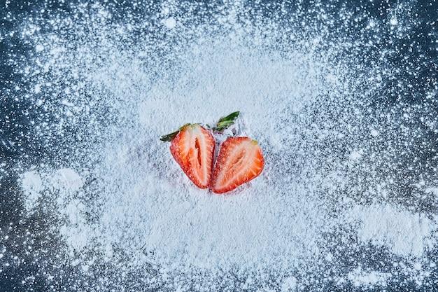 粉末で青い表面に新鮮なイチゴのスライス