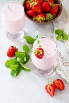 회색 돌 또는 슬레이트에 신선한 딸기 스무디와 신선한 딸기