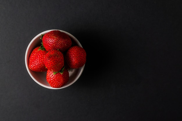 Fresh strawberry in white  bowl on black background.