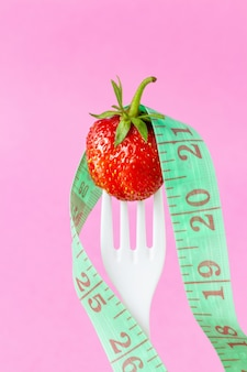 Fresh strawberry on white plastic fork with measuring tape