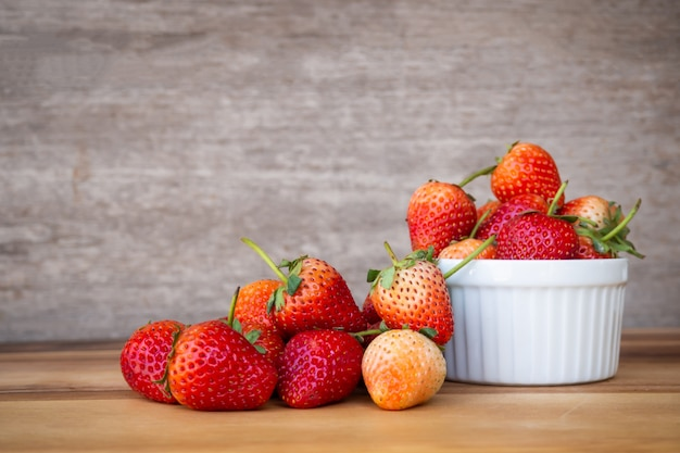 Fresh strawberry in white small bowl on wooden table.