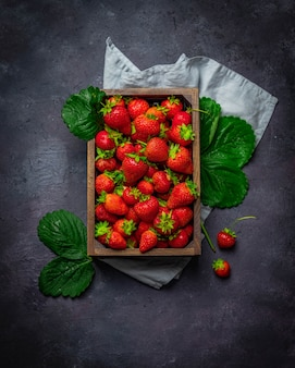 Fresh strawberry with green leafs in a wooden box