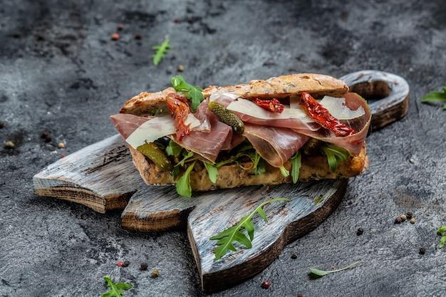 生ハム、サンドライトマト、ガーキン、パルメザンチーズ、ルッコラを添えた新鮮なサブマリンサンドイッチ。バナー、メニュー、テキストのレシピの場所、上面図。