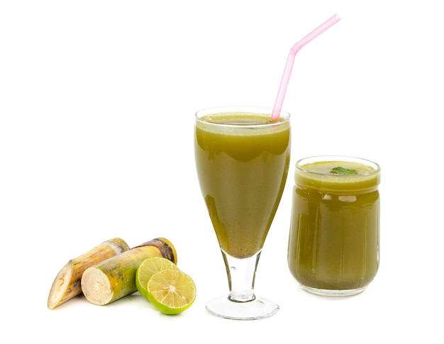 Fresh sugar cane juice in glass with cut pieces cane on isolate surface