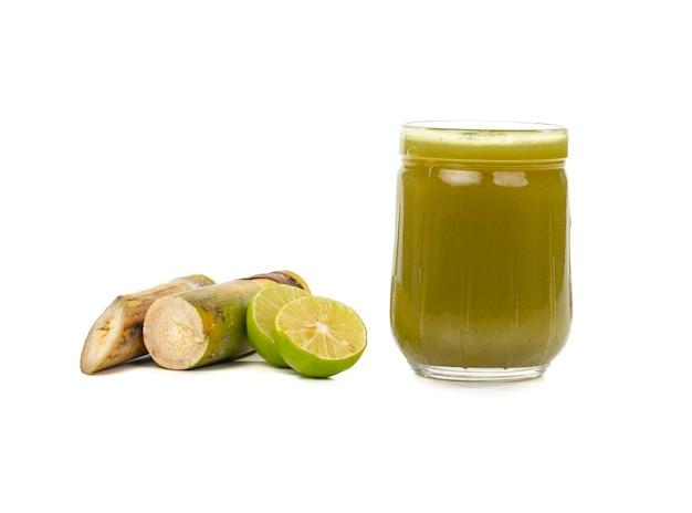 Свежий сок сахарного тростника в стакане с кусочками тростника на изолированной поверхности