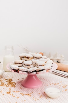 Fresh sugary dessert stacked on cake stand with ingredients against white wall