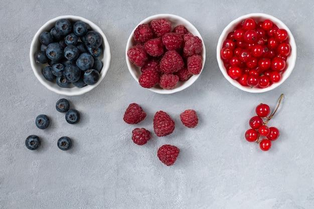 Свежие летние ягоды: вид сверху черники, малины и красной смородины